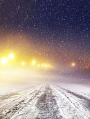 stock photo of sleet  - Snow covered winter road with shining streetlights at night - JPG