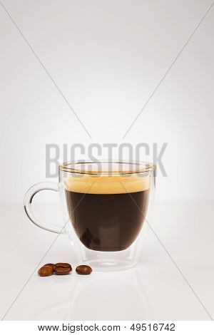 espresso in a glass cup with coffee beans