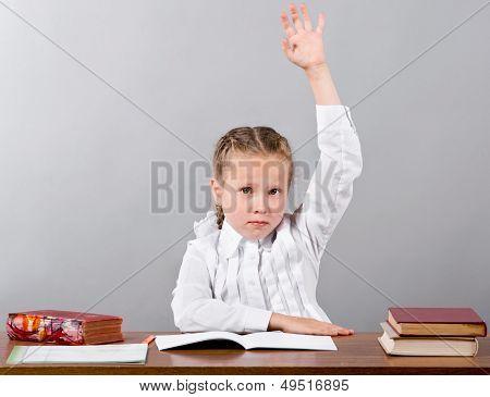 Schulmädchen sitzen am Schreibtisch heben ihre Hand zu wissen die Antwort
