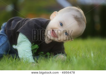 Iinfant Sits And Laughing On The Grass