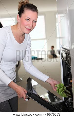 Smiling Woman Removing A Hot Pan From The Oven
