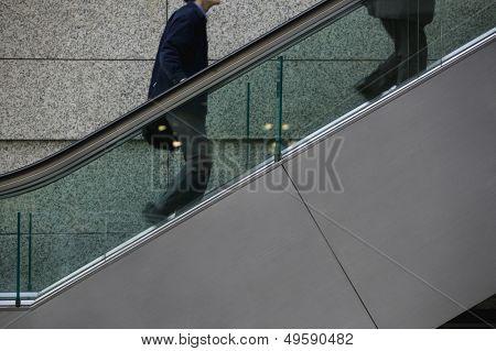 Japan Tokyo Tokyo International Forum two men ascending escalator mid section
