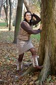 stock photo of leg warmer  - Autumn woman wearing leg warmers leaning tree in the park - JPG