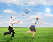 pic of runaway  - Scared young female trying to runaway from man running with butterfly net outdoor - JPG