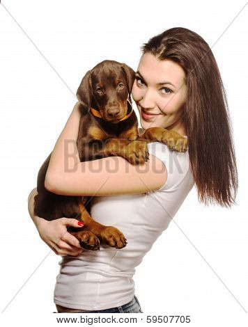 Brunette girl with her doberman puppy isolated on white background