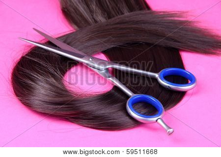 Long brown hair with scissors on pink background