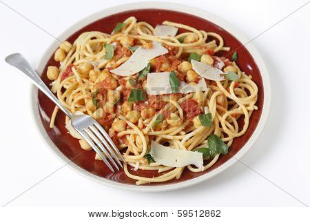Spaghetti with a chickpea, tomato and chilli flakes sauce, garnished with fresh torn basil leaves and flakes of parmesan. This is a traditional Italian dish called spaghetti alla ceci