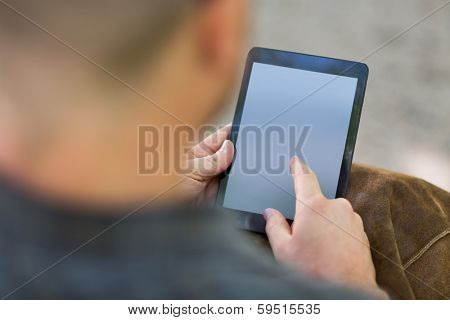 Cropped image of male university student using digital tablet at campus