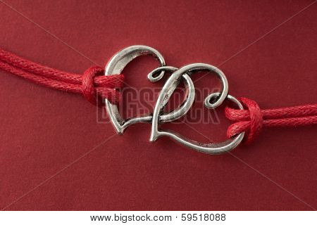 Two hearts connected, on red background.
