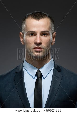 Front view of self-confident male in dark suit with black tie. Concept of professionalism and success in business