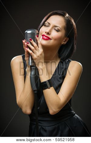 Half-length portrait of female singer with closed eyes wearing black evening dress and keeping mike on grey background. Concept of music and retro fashion
