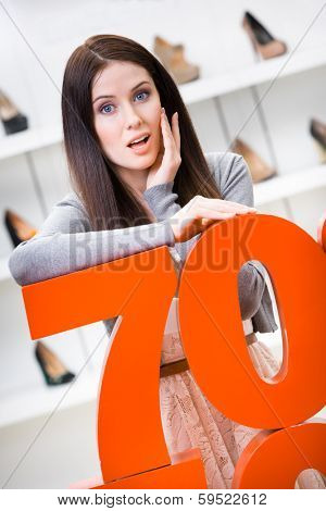 Woman showing the percentage of sales on shoes in the shopping center against the window case with pumps
