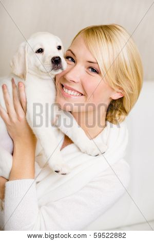 Woman keeping white puppy of Labrador near her face