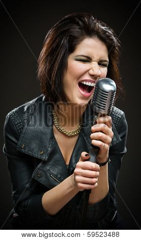 Half-length portrait of female rock singer wearing black jacket and keeping microphone on grey background. Concept of music and rave