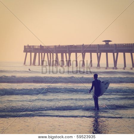 Surfing at the pier in the early morning with retro effect.