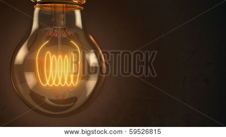 Close Up Of An Illuminated Vintage Hanging Light Bulb Over Dark Background
