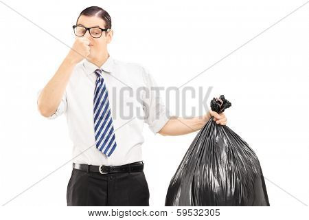 Male closing his nose and holding a stinky garbage bag isolated on white background