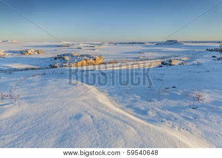prairie with rock outcroppings covered by snow at sunset, northern Colorado at Natural Fort