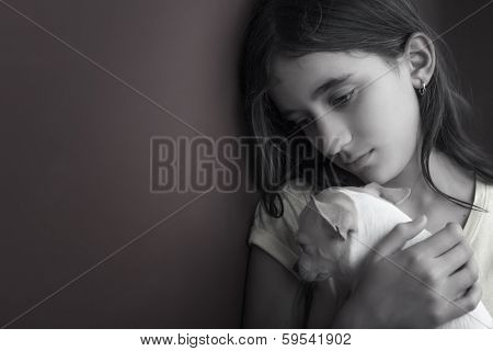 Sad and lonely girl and her small dog leaning against a wall