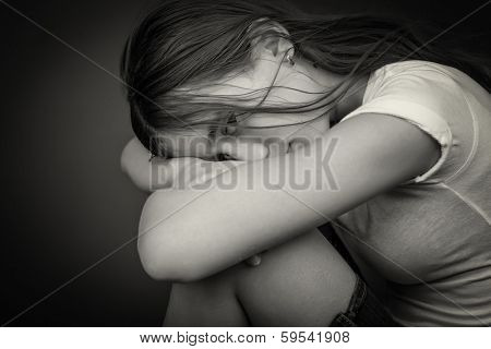 Black and white image of a sad and lonely girl with her head resting on her legs and looking at the camera