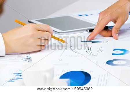 Close up of human hands and documents with graphs and diagrams