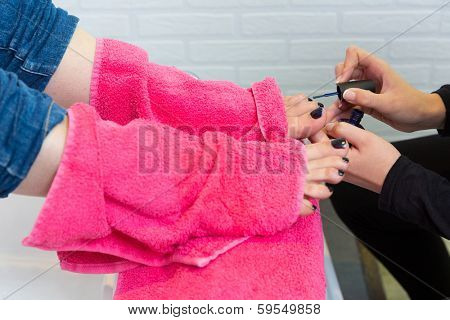 Pedicure chair spa and woman hands painting toes nail polish after bath with pink towel