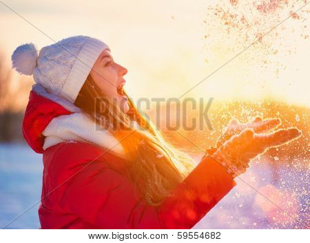 Beauty Winter Girl Blowing Snow in frosty winter Park. Outdoors. Flying Snowflakes. Sunny day. Backlit. Beauty young woman Having Fun in Winter Park. Good mood