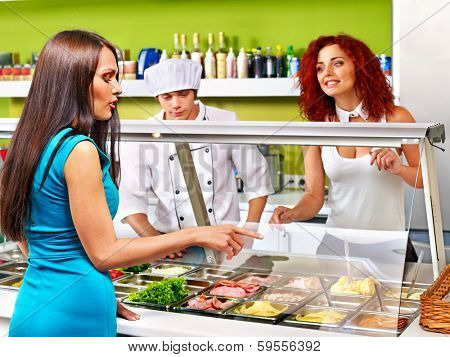 Young woman at cafeteria buying food.