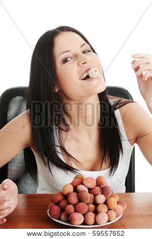 Young beautiful caucasian woman eating litchi fruits, isolated on whiet background