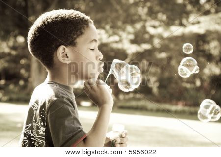 African american boy blowing bubbles
