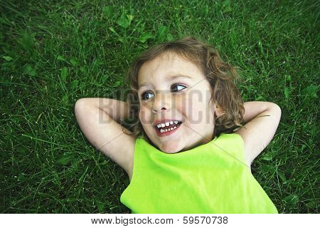 a young girl laying in the grass