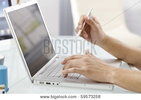 Closeup photo of male hands typing on laptop keyboard, holding pen.