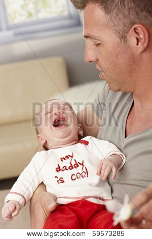 Closeup photo of father holding crying baby. My daddy is cool is written on baby's top.