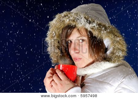 Snowing On Young Woman Drinking Something Hot