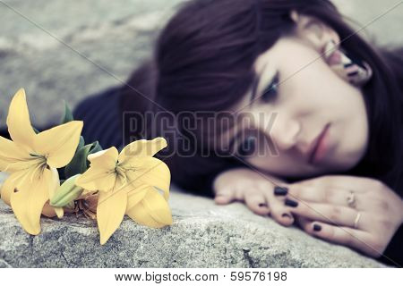 Sad young woman lying on the tombstone