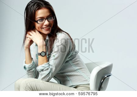 Young cheerful businesswoman sitting on the chair on gray background