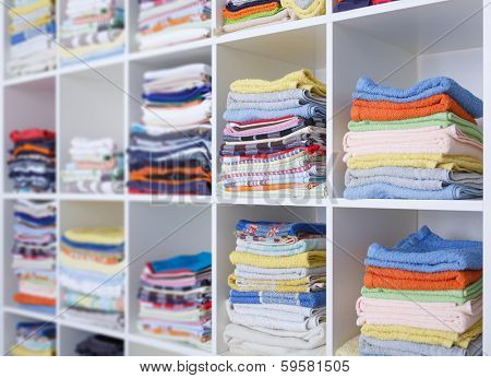 towels, bed sheets and clothes on the shelf