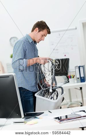 Businessman Putting Computer Cables In A Bin