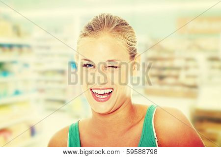 Happy young blond woman in store blinking.