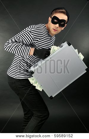 Thief with metal briefcase on dark background