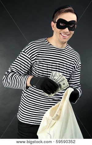 Thief with bag on dark background