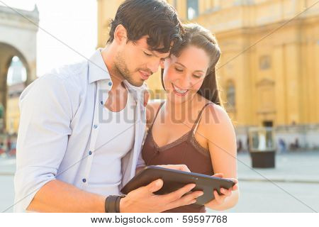 Man and woman or young couple making trip as tourists in Munich at the Odeon Church with city map on the tablet computer for navigation