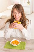 Beautiful young woman eating cornflakes and drinking morning coffee at home