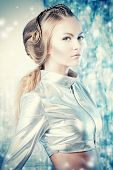 Close-up portrait of a beautiful young woman in silver latex costume with futuristic hairstyle and m