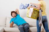 stock photo of laundry  - A woman with a laundry basket and a man watching tv