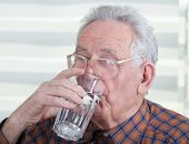 picture of water shortage  - Old man with reading glasses holds and drinks glass of water - JPG