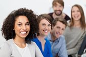 stock photo of cheer up  - Successful enthusiastic multiethnic business team led by a beautiful young African American businesswoman posing together in a row with focus to the woman - JPG