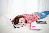 picture of boredom  - red haired student business woman lying asleep on her laptop on a white background - JPG
