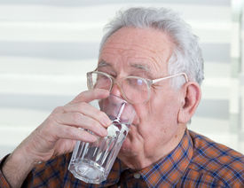 pic of water shortage  - Old man with reading glasses holds and drinks glass of water - JPG