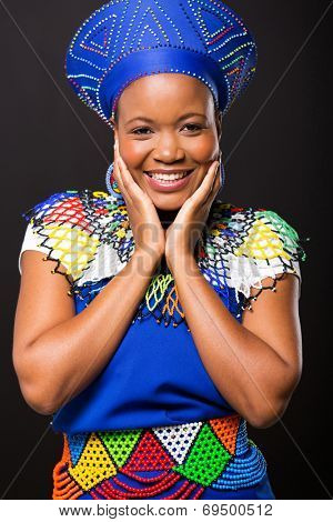 portrait of happy zulu woman on black background